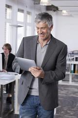 Deutschland, arbeiten Bayern, München, Erwachsene mit Tablet-PC, Kollegen im Hintergrund