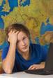 Teenager mit Laptop und Landkarte