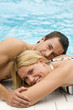 Deutschland, junges Paar am Schwimming-Pool