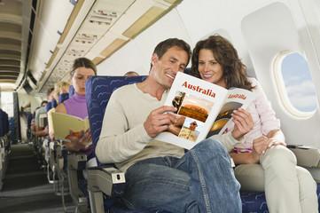 Deutschland, München, Bayern, Passagiere lesen in der Economy-Klasse Verkehrsflugzeug