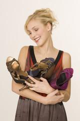 Junge Frau, die Schuhe in den Armen haltend