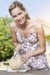 Italien, Toskana, Magliano, junge Frau schneidet Honigmelone, Lächeln
