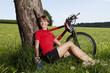 Deutschland, Bayern, Junge Frau sitzt gegen Baum mit Mountainbike