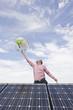 Deutschland, München, erwachsener Mann balanciert Globus auf dem Finger, Solaranlage
