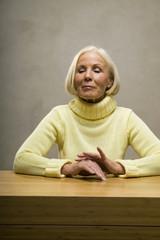Ältere Frau sitzt am Tisch