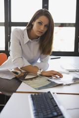 Junge Frau im Büro liest Zeitschrift