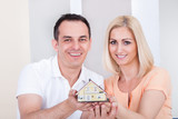 Couple holding house model