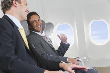 Deutschland, Bayern, München, Geschäftsleute sprechen in der Business Class Flugzeugkabine