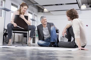 Deutschland, Bayern, München, Männer und Frauen diskutieren im Büro