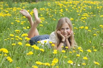 Österreich, Teenager-Mädchen liegt auf Blumenwiese
