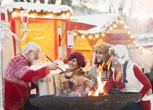Österreich, Salzburg, erwachsener Mann, serviert Getränke an Jugendliche, Weihnachten