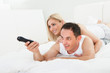 Woman Lying On Man's Back Watching Television