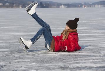 Österreich, Teenager-Mädchen auf der Eisbahn beim Schlittschuhlaufen gefallen