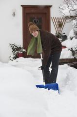 Österreich, Junger Mann beim Schneeschaufeln vor dem Haus