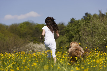 Deutschland, Baden Württemberg, Tübingen, Mädchen mit Hund, läuft durch Wiese, Rückansicht