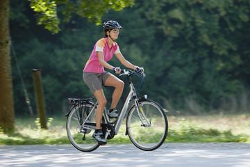 Deutschland, Bayern, München, Frau auf Elektro-Fahrrad