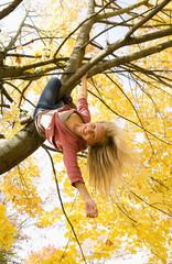 Österreich, Teenager-Mädchen hängt im Ahornbaum im Herbst