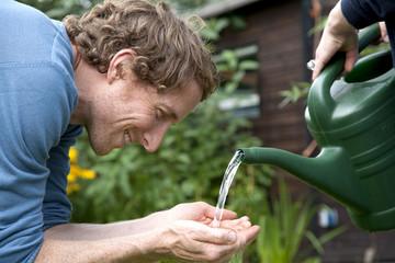 Mann wäscht sich mit Wasser aus Gießkanne