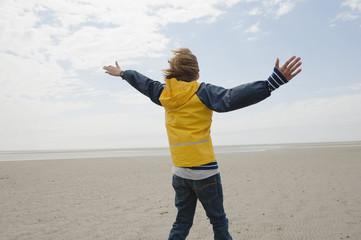 Deutschland, St.Peter-Ording, Nordsee, Junge in Regenmantel steht am Strand, Arme nach oben