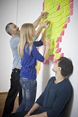 Deutschland, Köln, Männer und Frau klebt Papier Hinweis auf Wand