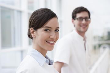 Deutschland, Bayern, Diessen am Ammersee, Zwei junge Ärzte lehnt am Geländer, Lächeln