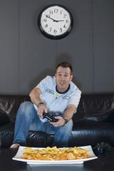 Mann sitzt auf der Couch und spielen Videospiele