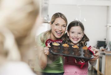 Deutschland, Köln, Mutter und Tochter halten Tasse Kuchen in Backblech