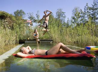 Österreich, Salzburger Land, Teenager spielen im Garten, Pool