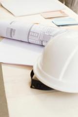 Helm auf Bauplan auf dem Tisch