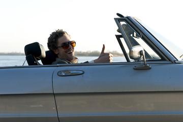Deutschland, Hamburg, Mann mittleren Alters fährt in altem Auto in der Nähe der Elbe