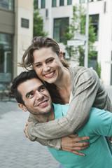Deutschland, Berlin, Mann mit Frau auf dem Rücken, in der Stadt