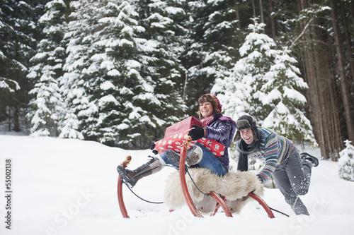 Österreich, Land Salzburg, Flachau, Junge Frau sitzt auf Schlitten mit Weihnachtsgeschenken