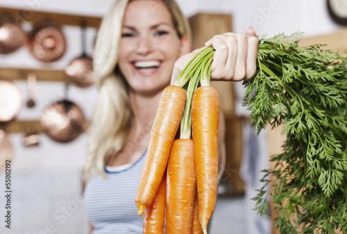 Italien, Toskana, Magliano, Junge Frau, die Karotten in Küche hält, Lächeln