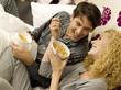 Junges Paar beim Frühstück im Bett, Lächeln