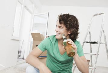 Deutschland, Köln, Junger Mann trinkt Bier , Wohnungsrenovierung