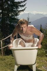 Junger Mann steigt aus der Badewanne