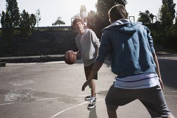 Deutschland, Berlin, Teenage Jungen spielen Basketball in Spielplatz