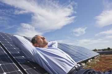 Deutschland, München, erwachsener Mann ruht auf Sonnenkollektor