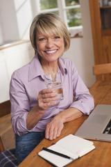 Deutschland, Kratzeburg, erwachsene Frau mit Wasserglas und Laptop