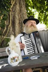 Deutschland, Bayern, Oberbayern, erwachsener Mann in traditioneller Tracht spielt Akkordeon in Biergarten