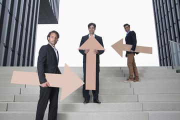 Deutschland, Nordrhein-Westfalen, Düsseldorf, Junge Unternehmer stehen auf einer Treppe mit Pfeilen in verschiedene Richtungen