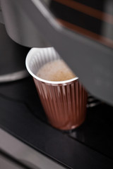Pouring hot espresso coffee in a glass