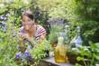 Österreich, Salzburger Land, Junge Frau im Garten, hockt unter Blumen