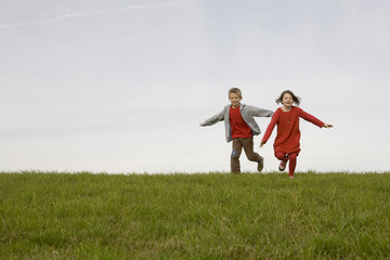 Junge und Mädchen in Wiese laufen ausgestreckten Armen