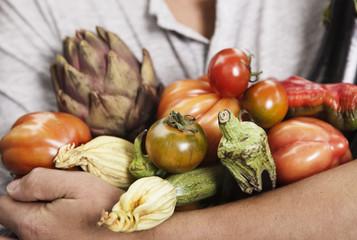 Italien, Toskana, Magliano, Nahaufnahme von jungen Mann hält verschiedene Gemüse