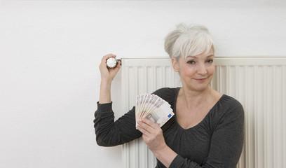 Deutschland, Düsseldorf, Frau mit Banknoten, Einstellen Heizung zu Hause
