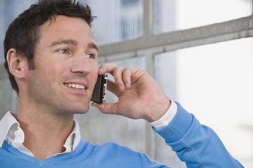 Deutschland, München, junger Mann vor dem Fenster mit Handy, Nahaufnahme
