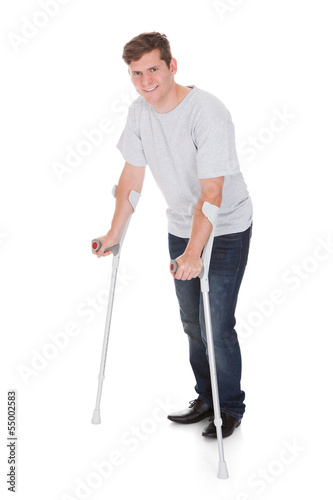 Young Man Walking With Two Crutches