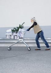 Deutschland, Junge Frau schiebt Einkaufswagen mit Geschenken