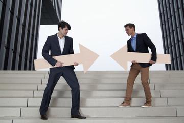 Deutschland, Nordrhein-Westfalen, Düsseldorf, Junge Unternehmer steen auf einer Treppe mit Pfeilen in verschiedene Richtungen